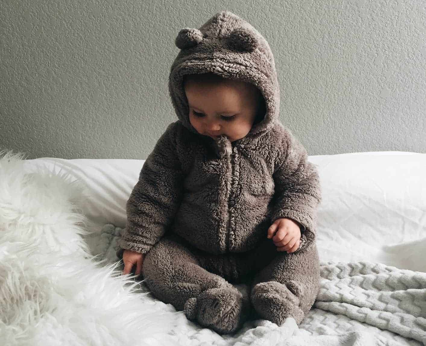 Baby in furry onesie sat on a cosy blanket