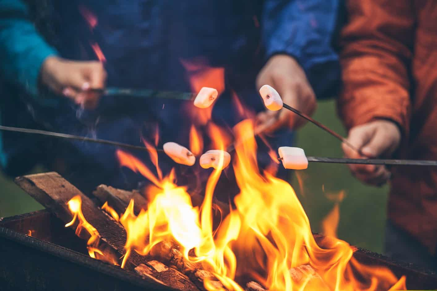 hands of friends roasting marshmallows over the fire