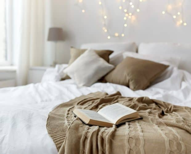 coziness comfort interior and holidays concept - cosy bedroom with